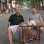 2 người đàn ông vác bàn ghế ra giữa đường uống trà