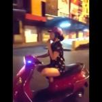 Cô gái vừa đi xe máy vừa chấp tay niệm phật