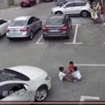 Kinh hoàng ô tô chèn qua 3 em bé đang ngồi chơi ở bãi đỗ xe