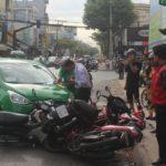 Xe taxi Mai Linh tông nhiều xe máy chờ đèn đỏ khi tránh xe đạp